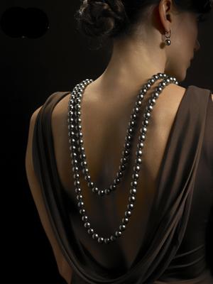 un collier long porté dans le dos avec perle de tahiti