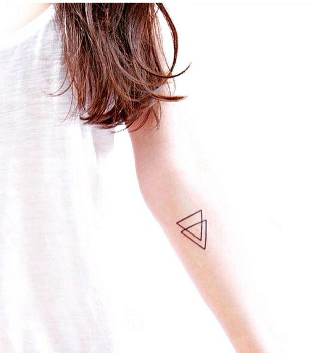 un tatouage minimaliste et gémotrique deux triangles simples et discrets
