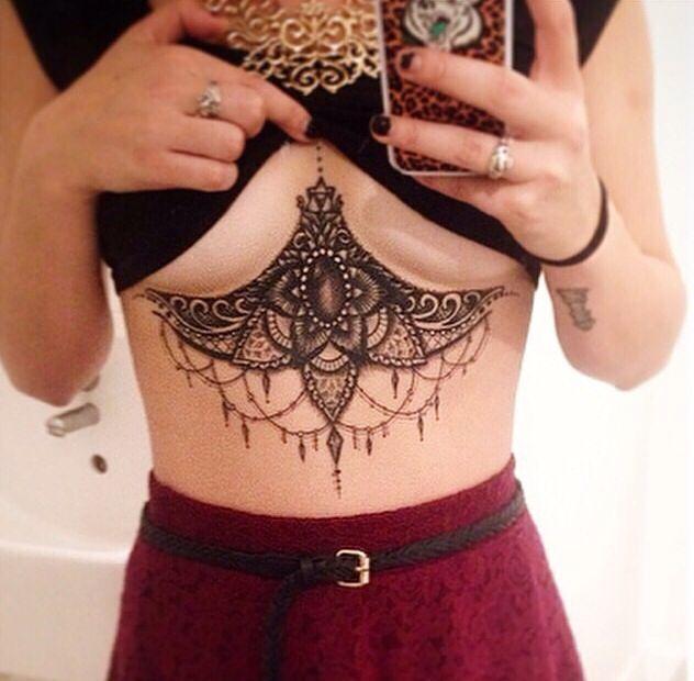 un tatouage sous la poitrine de style baroque réussi