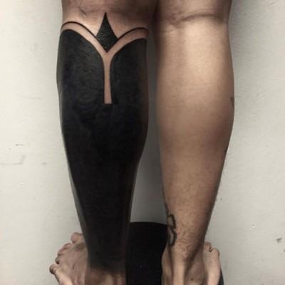 un tatouage recouvrant entièrement à l'encre noire un mollet